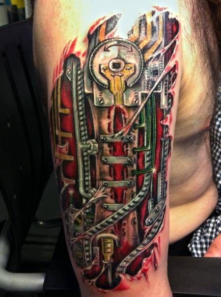 biomechaniczne tatuaże na ramieniu