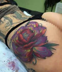 kwiatek tatuaż na pośladku