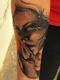 twarz kobiety tatuaż na przedramieniu